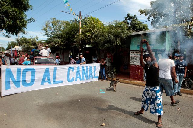 """A protester fires a homemade mortar in front of a banner that reads """"No to Canal"""" during a protest march against the construction of the Interoceanic Grand Canal, in Ometepe Island, Nicaragua January 7,2017. (Photo by Oswaldo Rivas/Reuters)"""
