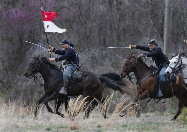 Union re-enactors charge Confederate troops during a re-enactment of the Battle of Appomattox Station, Wednesday, April 8, 2015, as part of the 150th anniversary of the surrender of the Army of Northern Virginia to Union forces at Appomattox Court House, in Appomattox, Va. (Photo by Steve Helber/AP Photo)