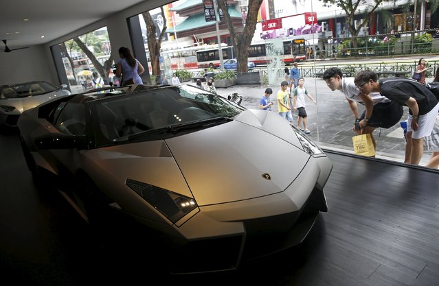 People look at a Lamborghini Reventon Roadster car on display at the shopping street of Orchard Road along with other rare and iconic super car models showcased by the Italian carmaker, in Singapore in this August 28, 2014 file photo. Sinagpore is expected to release inflation data this week. (Photo by Edgar Su/Reuters)