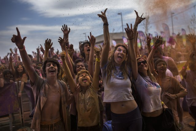 Revelers, covered in coloured powder, celebrate, during a Holi Run Festival in Madrid, Spain, Sunday, April 12, 2015. Thousands of revelers took part in the festival that includes a mini marathon. The festivals are fashioned after the Hindu spring festival Holi, which is mainly celebrated in the north and east of India. (Photo by Andres Kudacki/AP Photo)