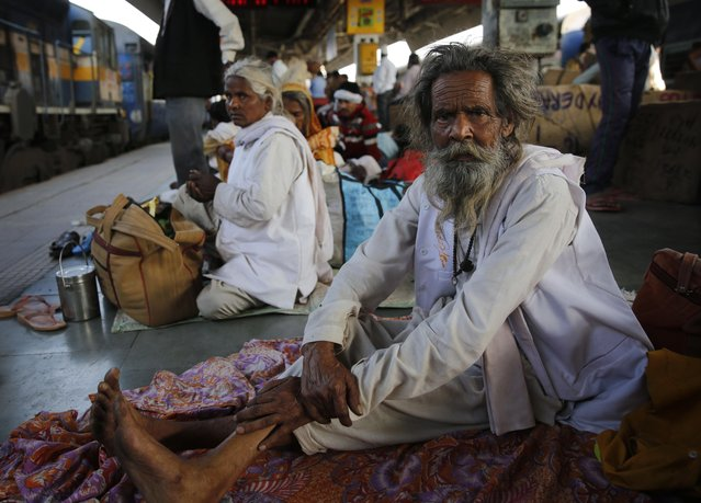 Indian travellers wait for their train to arrive at the railway station in Allahabad, India, Thursday, February 25, 2016. Indian railway minister Suresh Prabhu Thursday unveiled the budget for one of the world's largest railways network that serves more than 23 million passengers a day. Once a pride of the Indian government, it's now hobbled by ageing infrastructure. (Photo by Rajesh Kumar Singh/AP Photo)