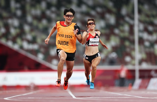 Uran Sawada of Team Japan (R) and guide Ryuhei Shiokawa compete in the Women's 100m - T12 Round 1 - Heat 3 on day 8 of the Tokyo 2020 Paralympic Games at Olympic Stadium on September 01, 2021 in Tokyo, Japan. (Photo by Molly Darlington/Reuters)