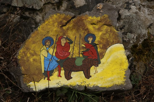In this photo taken on Saturday, April, 4, 2015  a religious style painting on stone depicts people hunting a bear at a shelter that attracts hundreds of visitors and volunteers from around the world every year, in Kutarevo, Croatia. (Photo by Amel Emric/AP Photo)