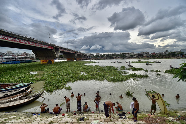 People bathe on the banks of Buriganga River during a lockdown imposed by the Bangladesh government to curb the spread of Covid-19 coronavirus in Dhaka on July 27, 2021. (Photo by Munir Uz Zaman/AFP Photo)