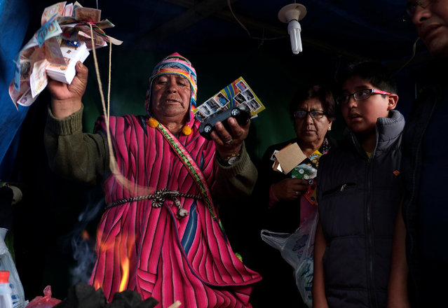 """An Aymara witchdoctor blesses goods of devotes during the """"Alasitas"""" fair, where people buy miniature versions of goods they hope to acquire in real life, in La Paz, Bolivia, January 24, 2017. (Photo by David Mercado/Reuters)"""