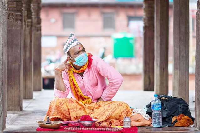 A Hindu priest seen waiting for devotees during the festival in Kathmandu, Nepal on August 22, 2021. During Janai Purnima or Rakchhya Bandhan festival people from Bhraman and Chhetri community take bath and change their Janai (a scared thread). Similarly, people from other communities get tied a Doro (sacred colorful thread) around their wrists. (Photo by SOPA Images Limited/Alamy Live News)
