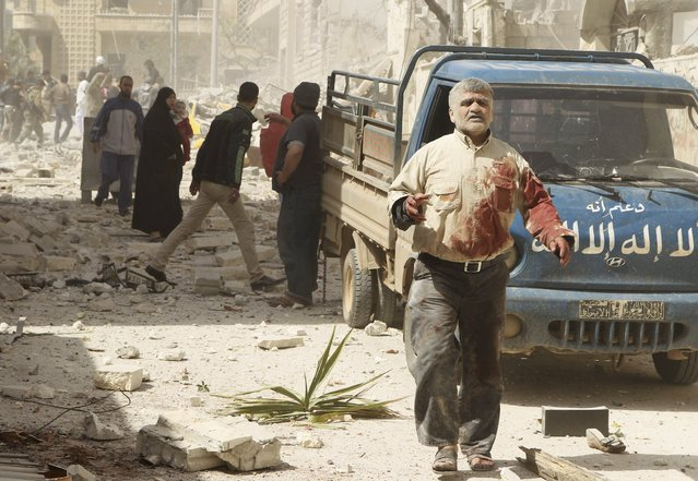 An injured man walks amid debris as residents reacts at a site hit by what activists said were barrel bombs dropped by forces of Syria's President Bashar al-Assad, at al-Thawra neighborhood in Idlib city April 20, 2015. (Photo by Ammar Abdullah/Reuters)