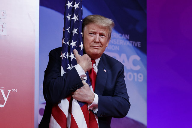President Donald Trump hugs the American flag as he arrives to speak at Conservative Political Action Conference, CPAC 2019, in Oxon Hill, Md., Saturday, March 2, 2019. (Photo by Carolyn Kaster/AP Photo)