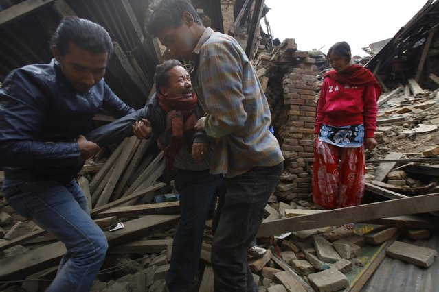 A Nepalese man cries after rescue workers found his mothers body amid earthquake debris in Bhaktapur near Kathmandu, Nepal, Sunday, April 26, 2015. (Photo by Niranjan Shrestha/AP Photo)