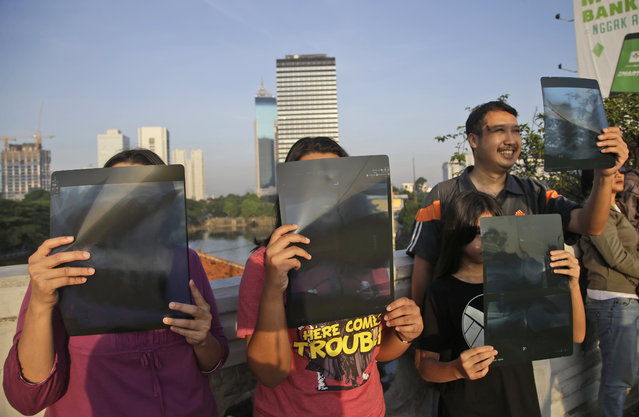 People watch a solar eclipse through x-ray films in Jakarta, Indonesia, Wednesday, March 9, 2016. (Photo by Tatan Syuflana/AP Photo)