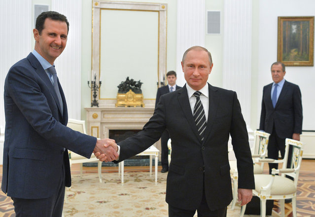 In this file photo taken on Tuesday, October 20, 2015, Russian President Vladimir Putin, center, shakes hand with Syrian President Bashar Assad as Russian Foreign Minister Sergey Lavrov, right, looks on in the Kremlin in Moscow, Russia. As another Syria war anniversary rolls in, the country appears to be at a critical juncture: For the first time in five years, external powers who have poured weapons and fighters into the conflict have signed on to a diplomatic framework to end the war, a two-week-old cease-fire is still holding and peace talks are scheduled to resume next week. (Photo by Alexei Druzhinin, RIA-Novosti, Kremlin Pool Photo via AP Photo)