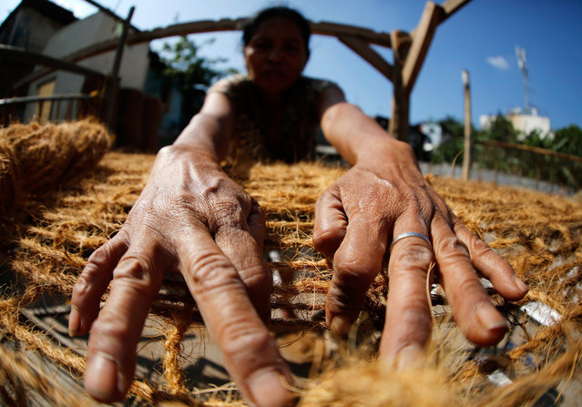 epaselect epa05195620 Filipino elderly woman Angelika Dela Vega waves coco-net at a slum area in Las Pinas city, south of Manila, Philippines, 05 March 2016. Rope making using coconut fibers created a source of livelihood to a number of vilagares who weave the coco coir into nets. (Photo by Francis R. Malasig/EPA)