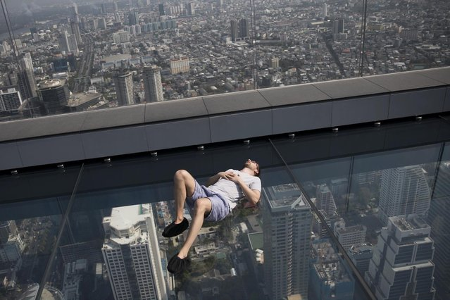 A man lies on the glass tray at MahaNakhon Skywalk atop King Power MahaNakhon on March 20, 2019 in Bangkok, Thailand. The tower opened in November 2018 and features Thailand's tallest observatory and rooftop bar. (Photo by Brent Lewin/Getty Images)