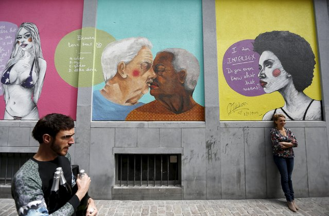 "A woman poses below the artwork of Greek artist Fotini Tikkou ""Out in the Street"", part of a giant fresco promoting lesbian, gay, bisexual and transgender (LGBT) street art and aiming to fight against homophobia and sexual discriminations in central Brussels, Belgium, May 1, 2015. (Photo by Francois Lenoir/Reuters)"