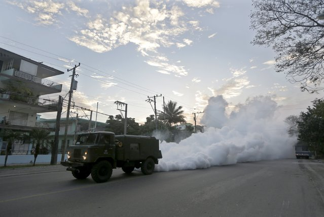 A military truck carries out fumigation in a neighborhood to stop the breeding of the dengue mosquito in Havana March 1, 2016. Cuba conducts regular fumigation inside homes to check the spread of dengue, a virus transmitted by the Aedes aegypti mosquito that causes a fever which can be deadly. The same mosquito can also spread the Zika virus, although the Cuban government says there have been no reported cases of the disease in the country. (Photo by Enrique de la Osa/Reuters)