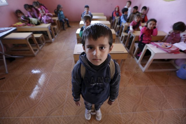 Five-year-old Wael al-Tawil poses inside a classroom in the rebel-controlled area of Maarshureen village in Idlib province, Syria  March 12, 2016. (Photo by Khalil Ashawi/Reuters)