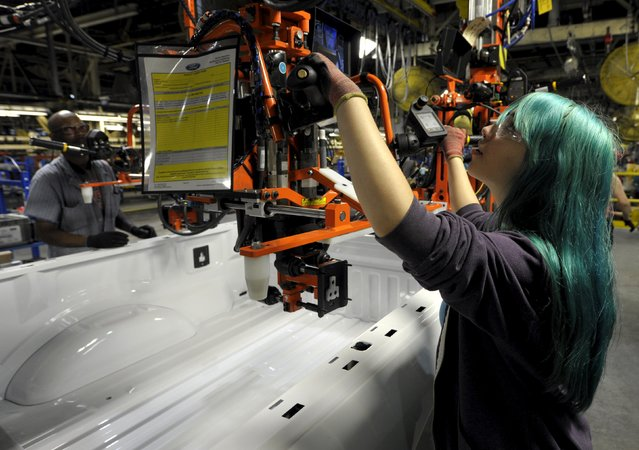 Auto worker Denell Sadler installs parts into the bed of a F150 at Ford's Kansas City Assembly Plant where new aluminum intensive Ford F-Series pickup is built in Claycomo, Missouri May 5, 2015. (Photo by Dave Kaup/Reuters)