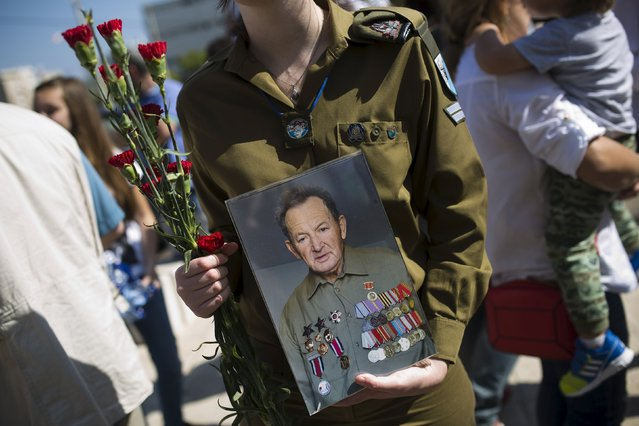 An Israeli soldier holds a photograph of a World War Two veteran during a parade marking the upcoming Victory Day, the anniversary of the Allied victory over Nazi Germany, in the southern city of Ashdod, Israel, May 8, 2015. (Photo by Amir Cohen/Reuters)