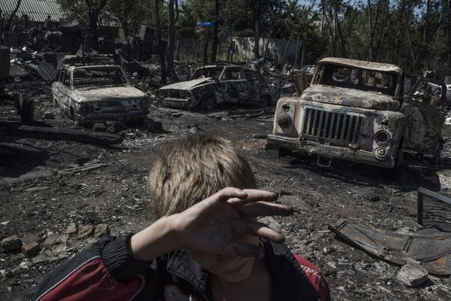 Cars burned by gunfire, July 2, 2014. Civilians escape from a fire at a house destroyed by an air attack in the Luhanskaya village. Ordinary people became victims of the conflict between self-proclaimed republics and the official Ukrainian authorities from 2014 onwards in the region of Donbass. Disaster came into their lives unexpectedly. These people were involved in the military confrontation against their will. They experienced the most terrible things: the death of their friends and relatives, destroyed homes and the ruined lives of thousands of people. (Photo by Valery Melnikov/Reuters/Rossiya Segodny/Courtesy of World Press Photo Foundation)