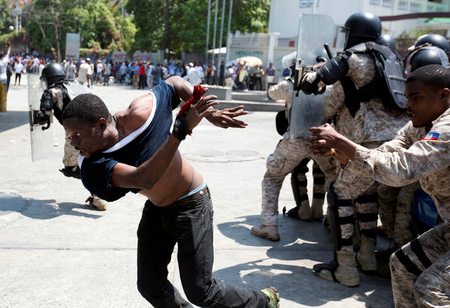 A demonstrator escapes from being detained outside the Superior Court of Accounts and Administrative Litigation during a protest against the alleged misuse of Venezuela-sponsored Petrocaribe funds by public officials, in Port-au-Prince, Haiti April 26, 2019. (Photo by Jeanty Junior Augustin/Reuters)