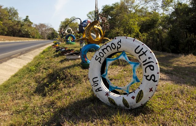 """A discarded tyre is used as a sign that reads """"We are still useful"""" in a shop located on the Panamerican highway near Catarina town May 8, 2015. (Photo by Oswaldo Rivas/Reuters)"""