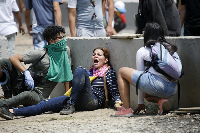Anti-government protesters take cover during clashes with security forces who are firing tear gas from La Carlota airbase in Caracas, Venezuela, Wednesday, May 1, 2019. (Photo by Ariana Cubillos/AP Photo)