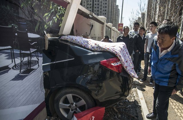 People look at a traffic accident site in Shenyang, Liaoning province, China, May 4, 2015. A car was driven into a wall of a construction site after the driver lost control on Monday, according to local media. (Photo by Reuters/China Daily)