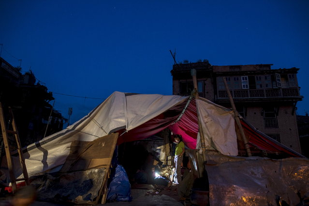 Local residents gather inside their temporary makeshift shelter after a fresh 7.3 earthquake struck, in Bhaktapur, Nepal, May 12, 2015. (Photo by Athit Perawongmetha/Reuters)