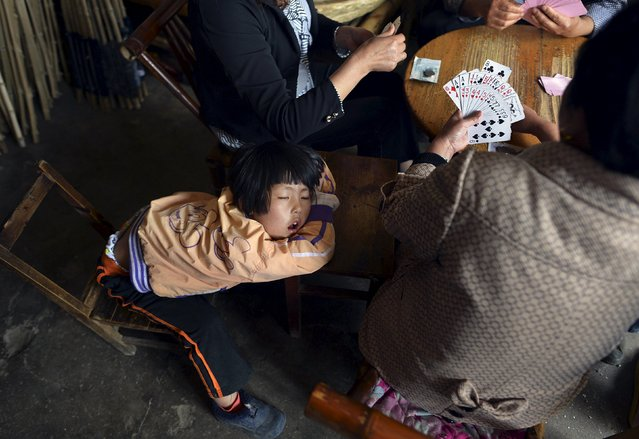 A girl sleeps as her family members play cards inside a small shop in Tongcheng, Anhui province, China, May 13, 2015. (Photo by Reuters/Stringer)