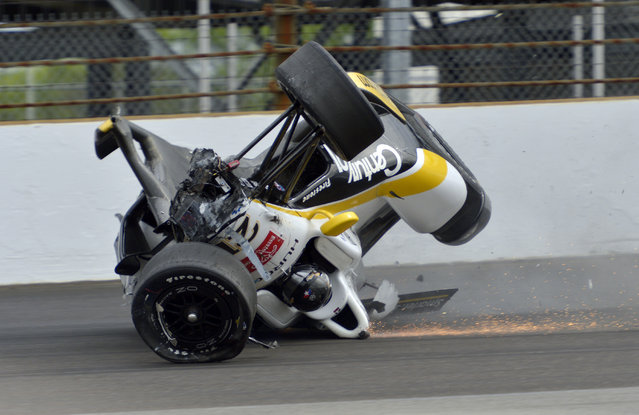 The car driven by Josef Newgarden slides down the track after hitting the wall in the first turn and going airborne during practice for the Indianapolis 500 auto race at Indianapolis Motor Speedway in Indianapolis, Thursday, May 14, 2015. (Photo by Marty Seppala/AP Photo)