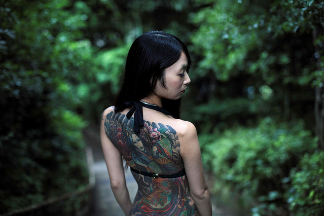 In this picture taken on June 12, 2018, Japanese model Yuki displays her tattoos as she poses for a photo at a park in Tokyo. Tattoos still provoke deep-rooted suspicion in Japan as the country prepares to host the 2020 Tokyo Olympics. People with body ink are refused entry to public swimming pools, bathing spots, beaches and often gyms, while visible body art can be harmful to job prospects. (Photo by Behrouz Mehri/AFP Photo)