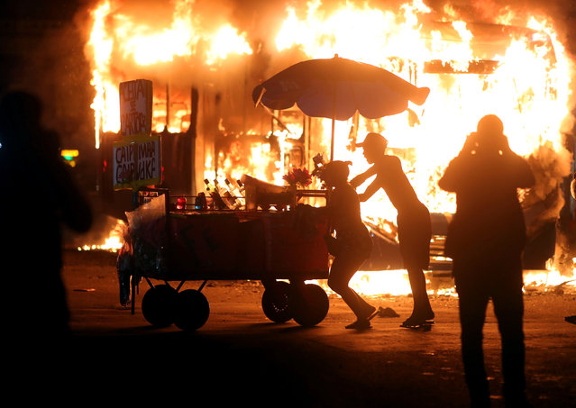 People pass by a bus set on fire during a protest against cuts to federal spending on higher education planned by Brazil's President Jair Bolsonaro's right-wing government, in Rio de Janeiro, Brazil May 15, 2019. (Photo by Ricardo Moraes/Reuters)