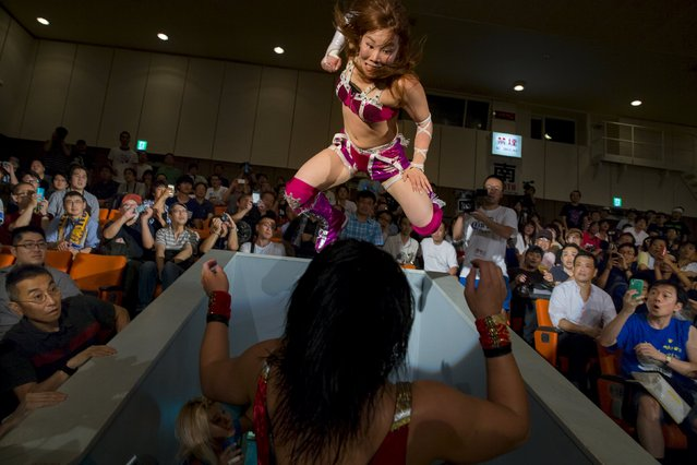 Wrestler Kairi Hojo (top) jumps at her opponent Mieko Satomura as they fight in the stands during a Stardom female professional wrestling show at Korakuen Hall in Tokyo, Japan, July 26, 2015. (Photo by Thomas Peter/Reuters)