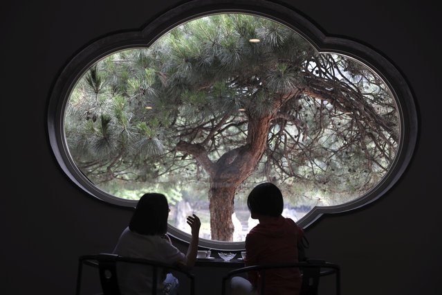 Visitors enjoy the scene from a window of the Xiangshan hotel designed by Chinese-American architect I.M. Pei and built in 1982 in Beijing, China on Friday, May 17, 2019. Pei, the globe-trotting architect who revived the Louvre museum in Paris with a giant glass pyramid and captured the spirit of rebellion at the multi-shaped Rock and Roll Hall of Fame, has died at age 102, a spokesman confirmed Thursday. (Photo by Ng Han Guan/AP Photos)
