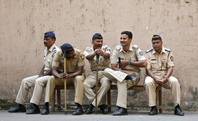 A policeman (C) yawns as he sits with his colleagues outside a court where the case of the gang-rape of a photojournalist was heard in Mumbai March 20, 2014. Four men were found guilty on Thursday of the gang-rape of a photojournalist last year in Mumbai, an attack that sparked street protests in the city and raised fresh questions about attitudes to women in the world's largest democracy. (Photo by Mansi Thapliyal/Reuters)