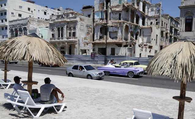 """People sit on deck chairs on an artificial beach as a bride and groom ride a classic American convertible car on the Malecon in Havana, Cuba, Thursday, May 21, 2015. The artificial beach is part of a collective artistic intervention named """"Behind The Wall"""" for the Havana Biennial Art Fair which starts on May 22. (Photo by Desmond Boylan/AP Photo)"""