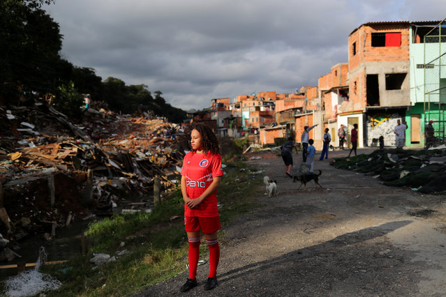 Vitoria Batista Oliveira, 14, stands as she waits for a boy to catch a missing ball during a training session of soccer in Jardim Peri Alto slum, on the outskirts of Sao Paulo, Brazil, June 5, 2019. (Photo by Amanda Perobelli/Reuters)