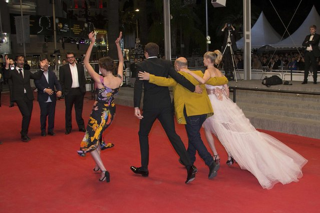 """(L-R) Cast members Aomi Muyock and Karl Glusman, director Gaspar Noe, cast member Klara Kristin run on the red carpet as they arrive for the screening of the film """"Love"""" out of competition at the 68th Cannes Film Festival in Cannes, southern France, May 21, 2015. (Photo by Yves Herman/Reuters)"""