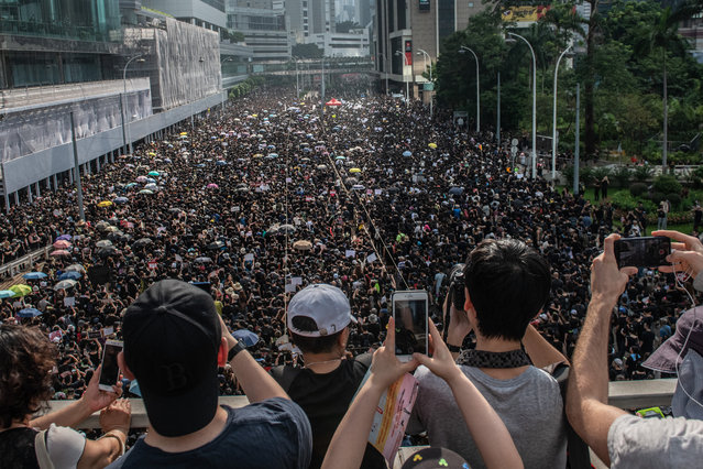 People take photographs as protesters match on the road below beneath during a demonstration against the now-suspended extradition bill on June 16, 2019 in Hong Kong. Large numbers of protesters rallied on Sunday despite an announcement yesterday by Hong Kong's Chief Executive Carrie Lam that the controversial extradition bill will be suspended indefinitely. (Photo by Carl Court/Getty Images)