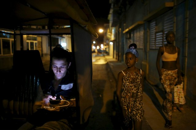 Self-employed pedicab driver Danilo Guerra, 25, uses his mobile phone as he waits for clients in downtown Havana April 12, 2016. (Photo by Alexandre Meneghini/Reuters)