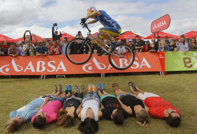 A stunt rider jumps over spectators after the final stage of the annual ABSA Cape Epic mountain bike stage race, Cape Town, South Africa, 30 March 2014. (Photo by Kim Ludbrook/EPA)