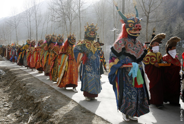 Lamas walk on a road to send evil spirits which have been killed, during the Tiaoqian praying ceremony