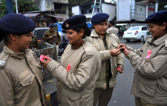 Indian policewomen tie ribbons onto each others uniforms in Dehradun on March 8, 2017, as they mark International Women' s Day. (Photo by AFP Photo/Stringer)