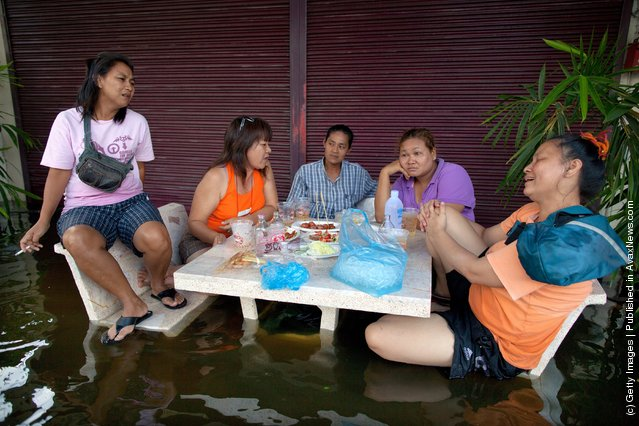 Thai women eat and drink whiskey to pass the time on a flooded street near the Chao Phraya river