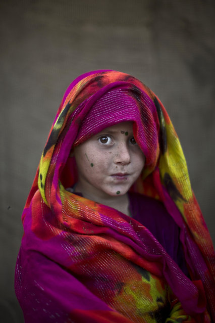 In this Friday, January 24, 2014 photo, Afghan refugee girl, Robina Haseeb, 5, poses for a picture, while playing with other children in a slum on the outskirts of Islamabad, Pakistan. (Photo by Muhammed Muheisen/AP Photo)