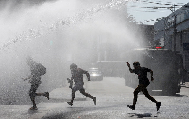 Student protesters run away as a riot police vehicle releases a jet of water during a demonstration to demand changes in the education system in Valparaiso, Chile, April 21, 2016. (Photo by Rodrigo Garrido/Reuters)