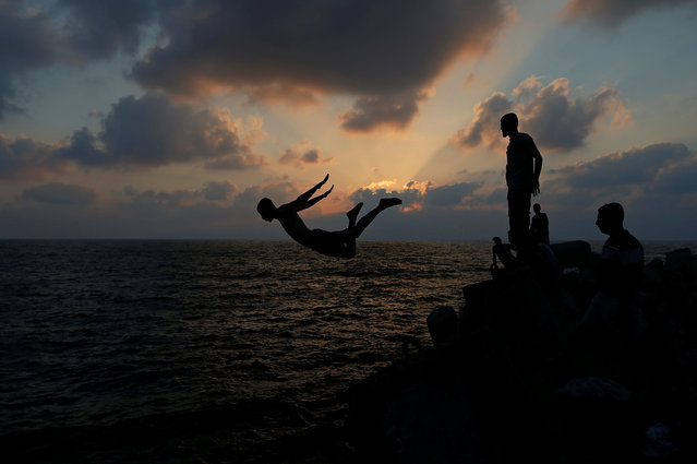 A Palestinian youth jumps into the water of the Mediterranean Sea on a hot day, at the seaport of Gaza City on June 28, 2019. (Photo by Mohammed Salem/Reuters)