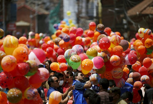 People hold balloons before releasing them during an event organized to commemorate the victims of last year's earthquakes in Kathmandu, Nepal, April 23, 2016. (Photo by Navesh Chitrakar/Reuters)