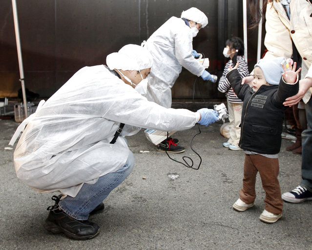 Officials in protective gear check for signs of radiation on children who are from the evacuation area near the Fukushima Daini nuclear plant in Koriyama, March 13, 2011. (Photo by Kim Kyung-Hoon/Reuters)