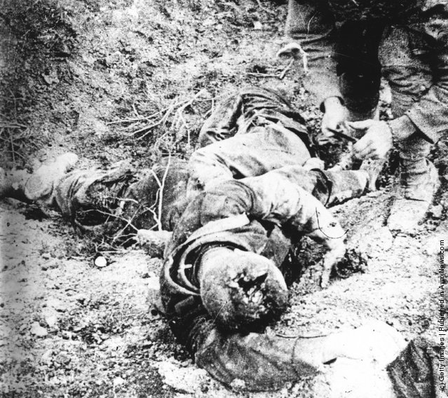 1915: A soldier kneels beside the corpse of a soldier killed in one of the Battles of Champagne (Dec 1914 - March 1915 and Sept - Oct 1915) fought between German and French armies on the Eastern Front